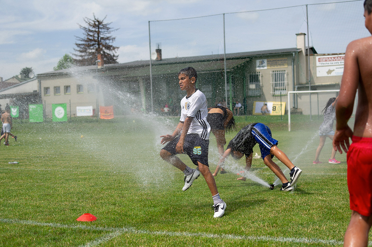 Young kids and children are enjoying water from sprinkler system on the football pitch, Action day, Olomouc, Czech Republic