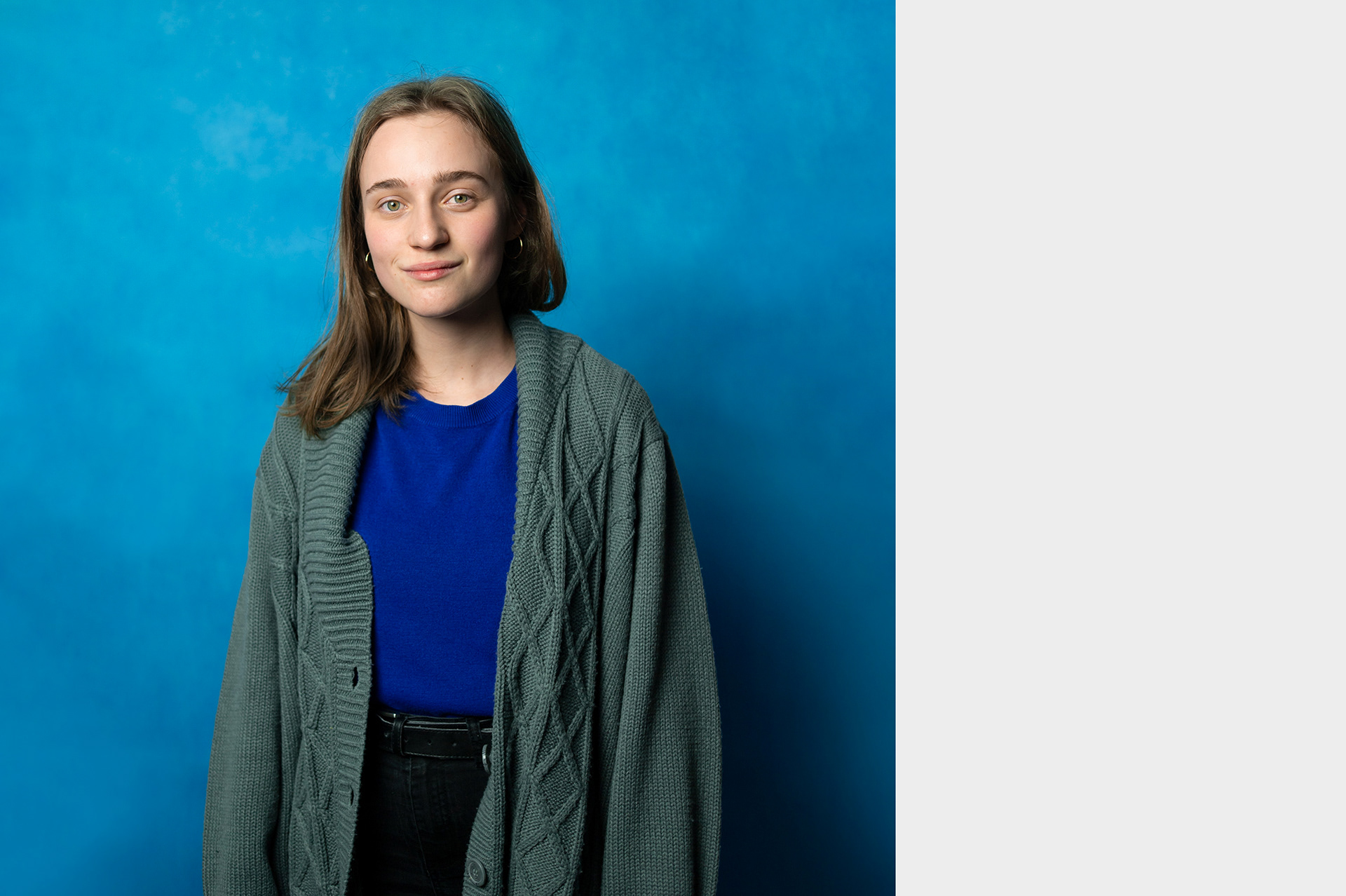 Adéla, studio portrait of young female volunteer in front of blue background