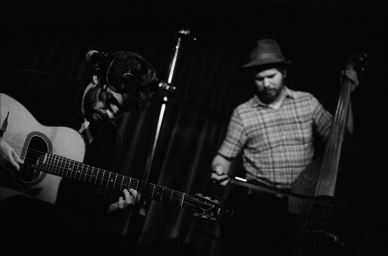 Concert photograph of two male musicians, guitarist and bassist, on the stage, Grégoire Brun, Vojtěch Vasko, Les Gars D'en Bas, Klub Hudební bazar, Ostrava, Czech Republic