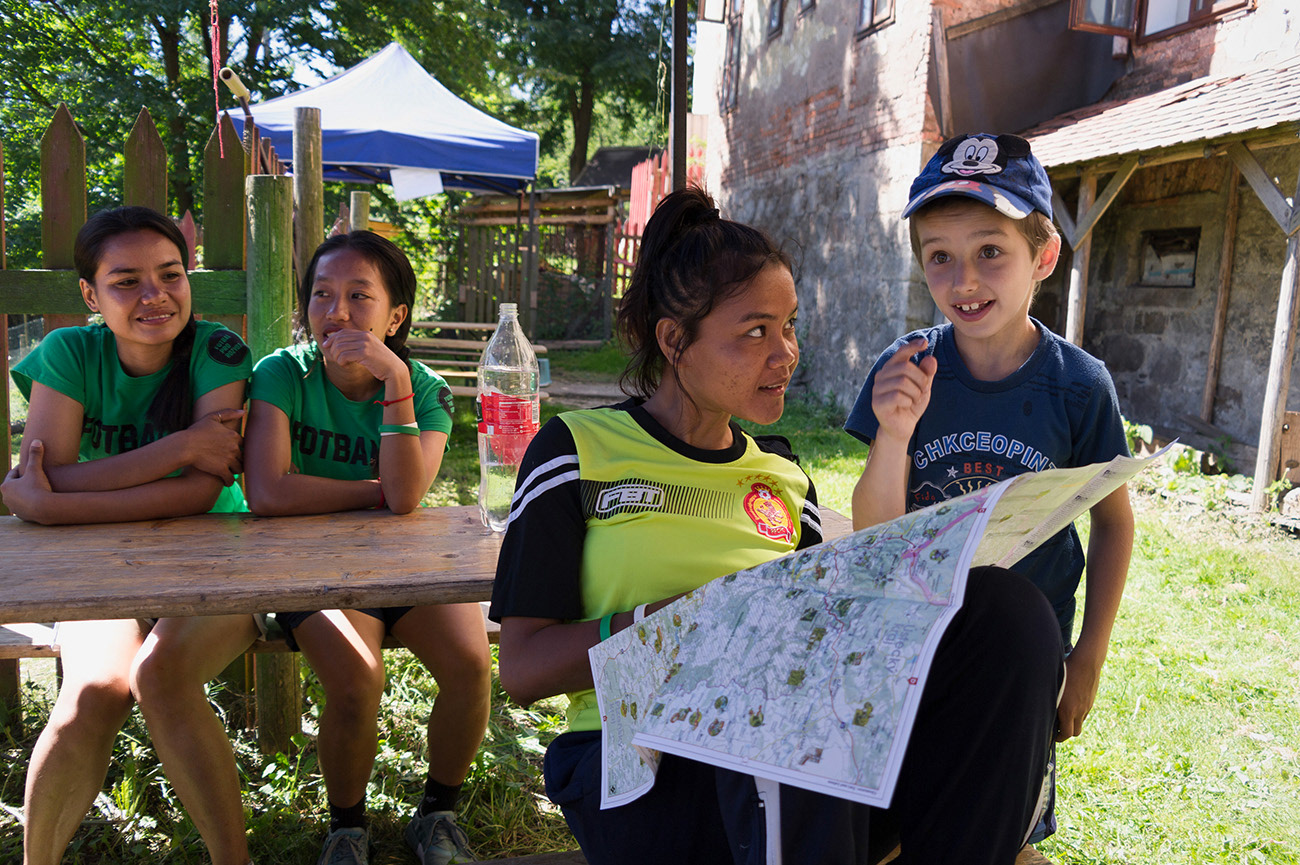Young asian women and child are reading in the map, Action day, Hřebeny, Josefov, Czech Republic