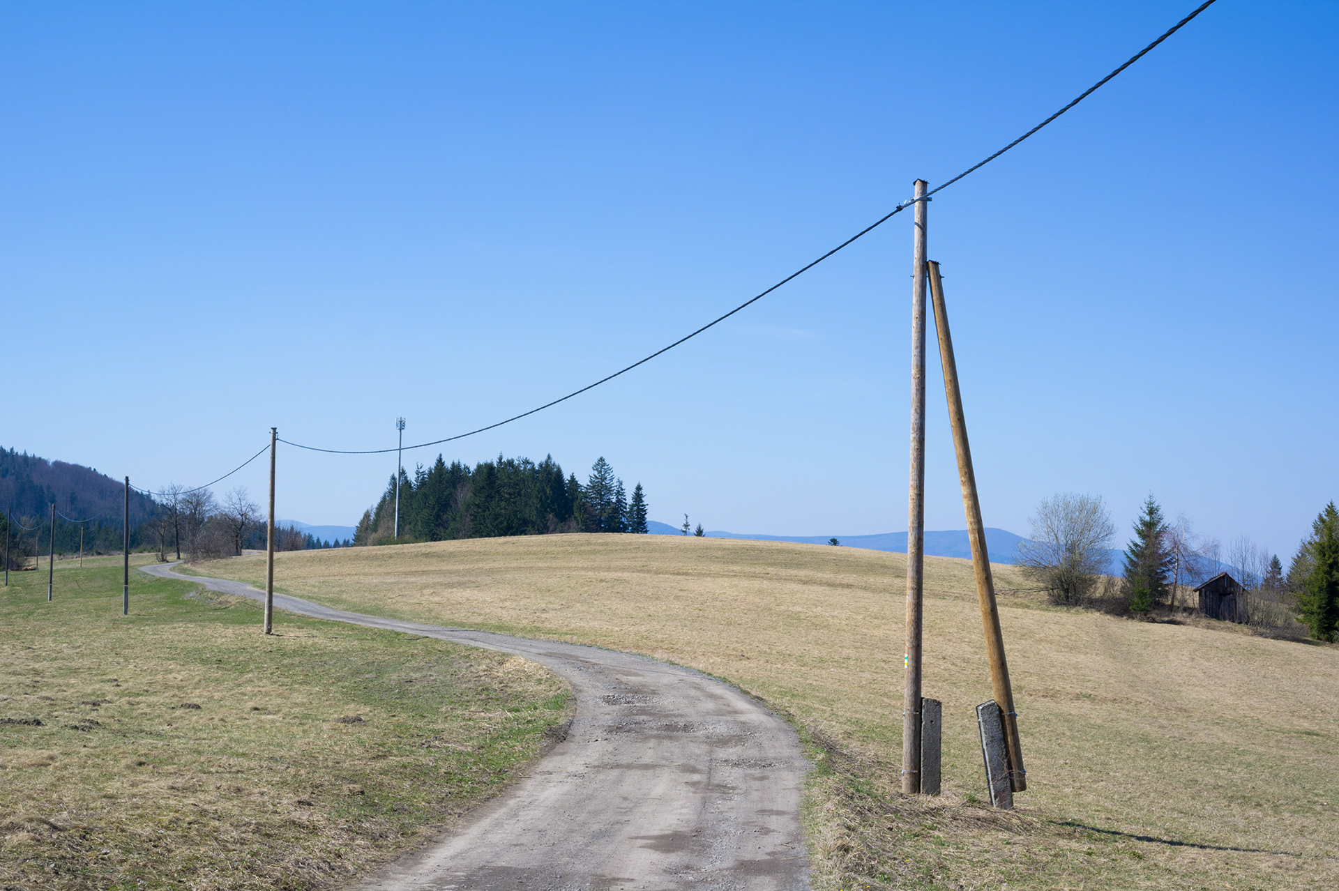 Rural area of field path and utility electrical power pole in early spring, Komorovský Grúň, Beskid mountains, Czech Republic