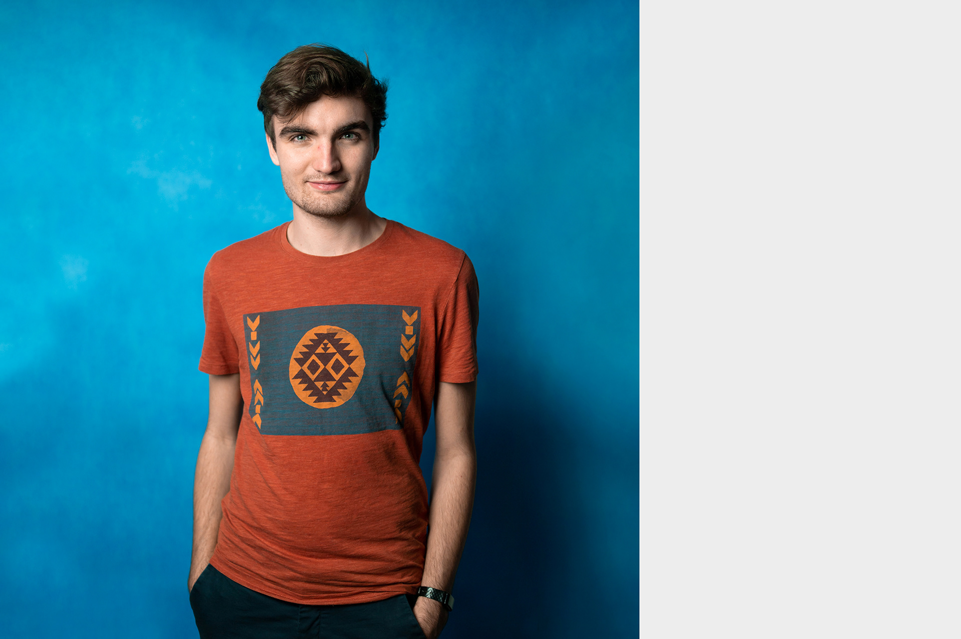 Michal, studio portrait of young male volunteer in front of blue background