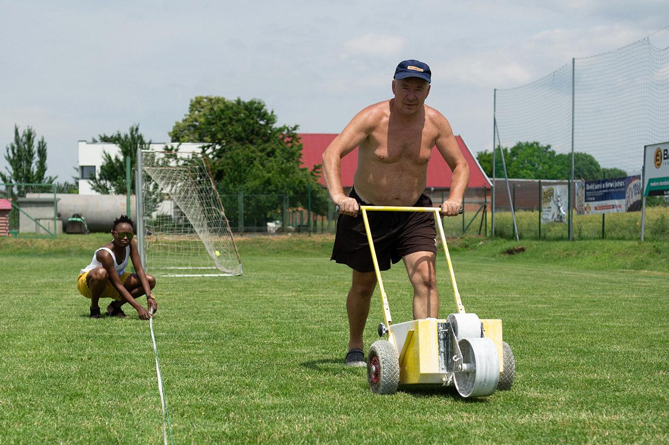 Older half naked man is preparing lines, Pitch preparation, Olomouc, Czech Republic