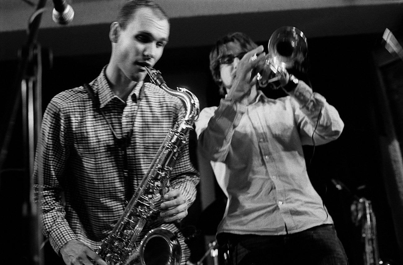 Concert photograph of male saxophone and trumpet musicians on the stage, Tomáš Zetek, Jan Štěpánek, Bandaband, Klub Parník, Ostrava, Czech Republic