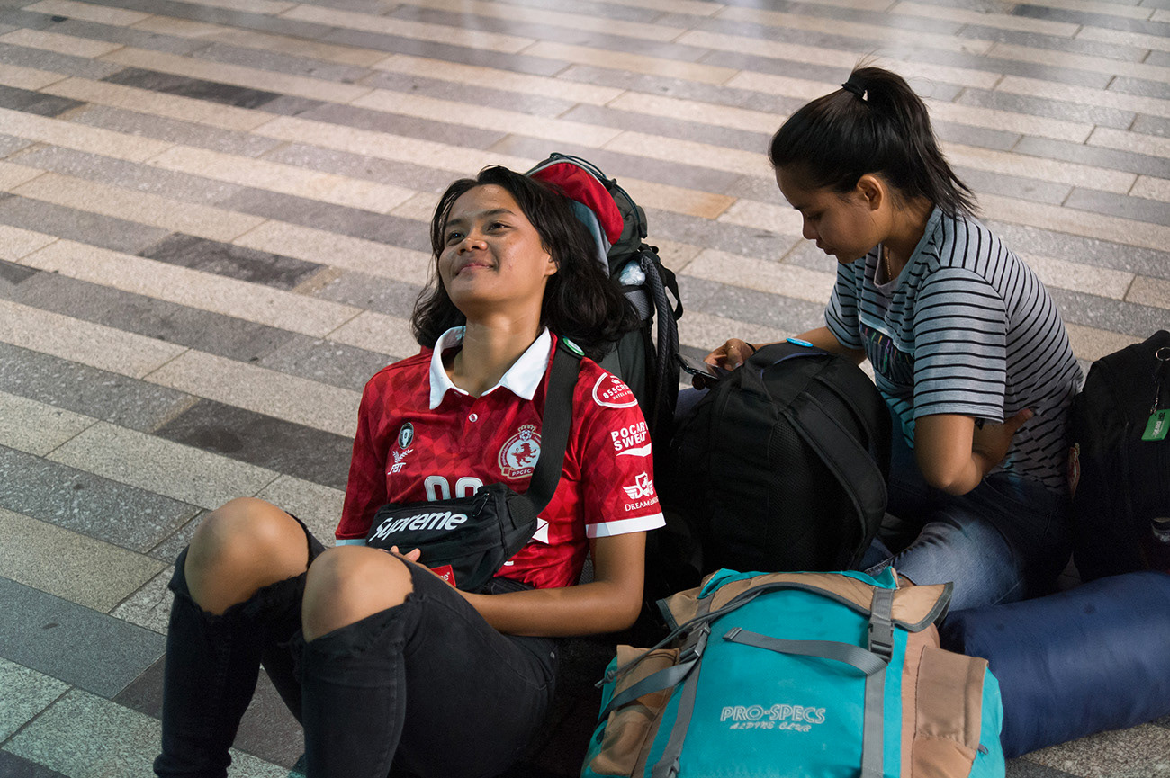 Young asian females are resting on the floor, waiting for train to Ústí nad Labem, Prague main railway station, Prague, Czech Republic